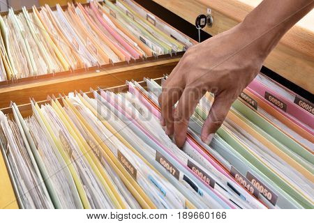 Hand of the employee search Financial documents stored in filing cabinets.
