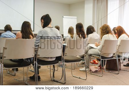 Women student during study, quiz, test, exams from teacher in lecture University classroom Speaker at business workshop and presentation. Audience at the conference room.
