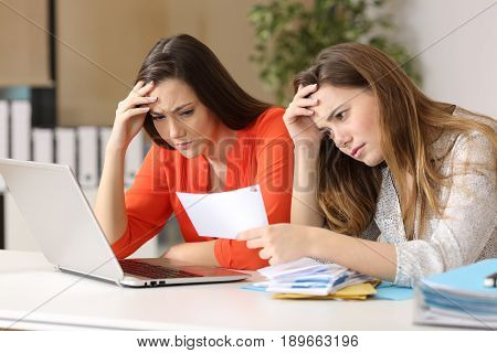Two worried coworkers reading a letter with bad news in a desk at office