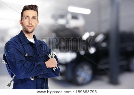 Auto mechanic with tools and workshop on background. Car service concept