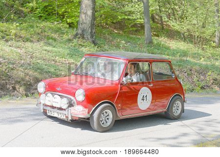 STOCKHOLM SWEDEN - MAY 22 2017: Red Mini Cooper S classic car from 1965 driving on a country road in the public race Gardesloppet in the forests at Djurgarden Stockholm Sweden. May 22 2017
