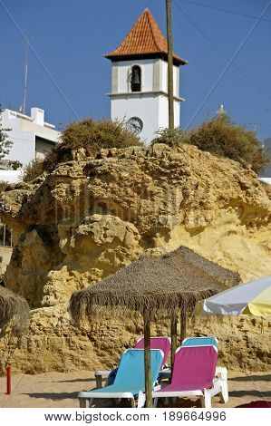 A rocky sand hill on the beach in Algarve. There's beach chairs and parasols in front of it and a white bell tower in the background.