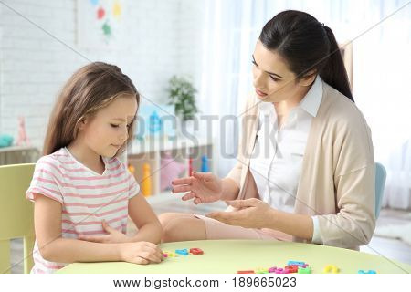 Young woman teacher and little girl on private lesson