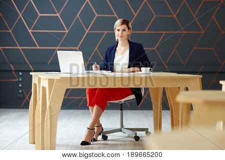 Confident employer sitting by workplace
