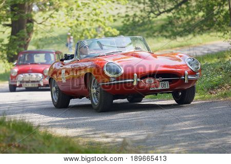 STOCKHOLM SWEDEN - MAY 22 2017: Red Jaguar E-Type classic car in a in the public race Gardesloppet in the beautiful forests in Djurgarden in Stockholm. May 22 2017 in Stockholm Sweden