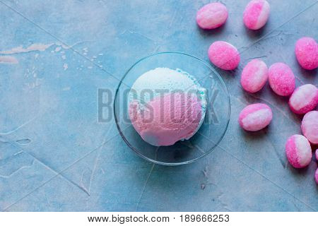 Blue and pink bubble gum ice cream with mint on concrete table background.