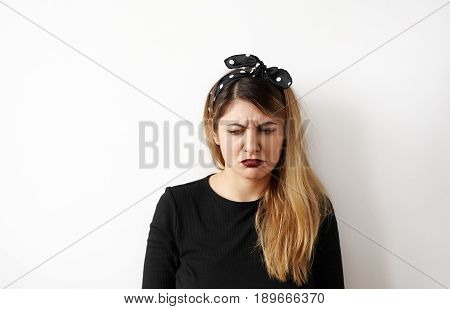 Negative human facial expression. Fashion beautiful girl resentfully pouted and looks away with irritated and offended face expression while standing isolated against white studio wall background