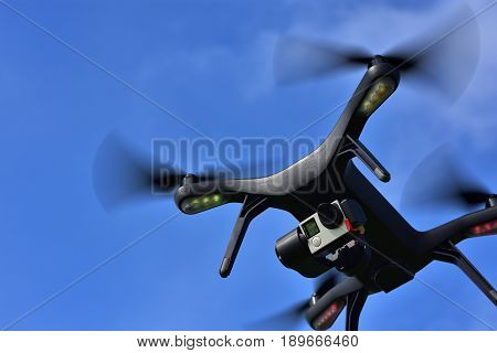 Black drone with camera flying over blue sky. Angle view copy space.