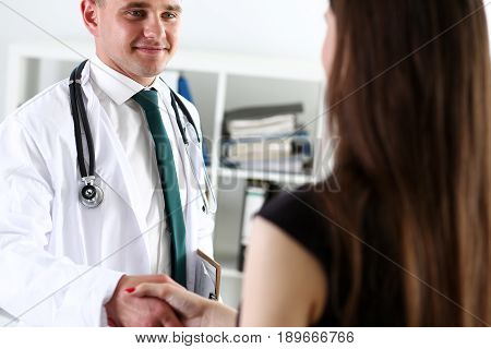 Handsome Male Doctor Shake Hand As Hello With Patient