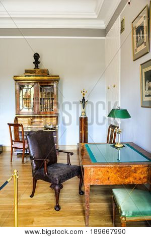 Ostafyevo, Moscow region - May 13, 2017 - Princely cabinet in an old mansion 18-19 centuries. Desk, armchair, bureau with a library, lamp, sculpture. Old furniture from Karelian birch and leather.