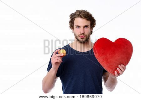 Young sexy macho holding red and yellow apple and big red toy heart isolated on white background. Concept of offer romance and Valentines day