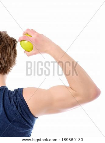 Guy with big muscles holds green apple in his hand isolated on white background. Concept of gym workout and healthy nutrition