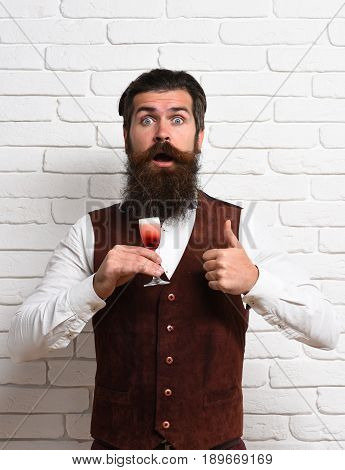 handsome bearded man with long beard and mustache has stylish hair on surprised face holding glass of alcoholic shot in vintage suede leather waistcoat on white brick wall studio background