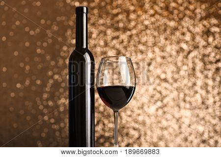 Glass Of Red Wine Near Dark Bottle On Metallic Background
