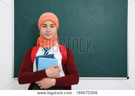 Cute girl with backpack and books standing near green school blackboard