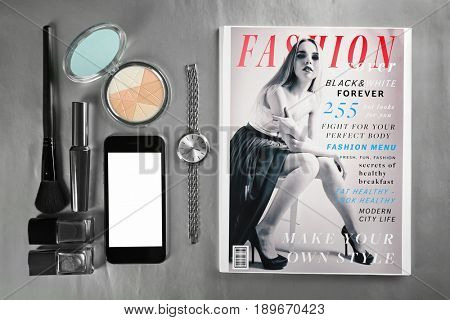 Cosmetics, wristwatch, smart-phone and magazine on grey background, top view