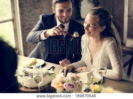 The groom feeding cake to the bride