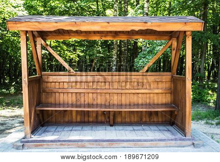Wooden gazebo with a bench in the forest