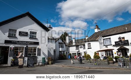 HAWKSHEAD UK - 23 APRIL 2017: The crowded whitewashed architecture of the village of Hawkshead in the heart of the English Lake District with tourists outside a small business shop and hotel.