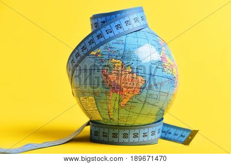 Globe wrapped with measuring tape on its poles isolated on warm yellow background. Symbol of globalization and worldwide population growth