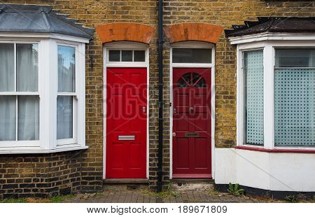 Traditional English house front entrance with red closed doors and white windows