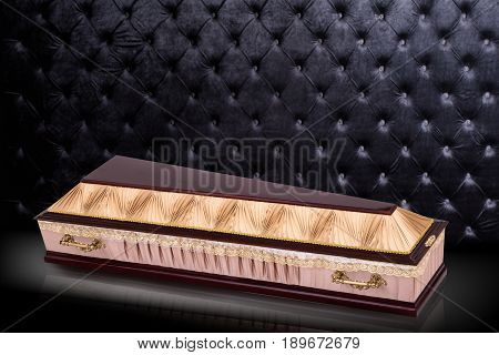 closed wooden beige coffin covered with cloth isolated on gray luxury background. casket with shadow on royal background. Ritual objects for burial. Surrender body dust of the earth. Christian funeral ritual