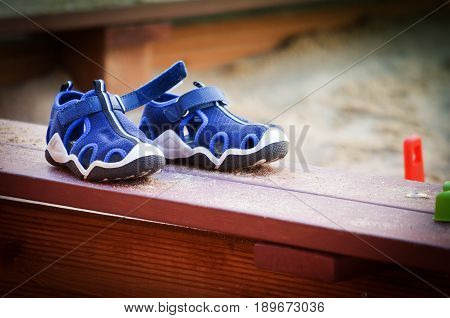 Children's Blue Running Shoes. Isolated on a Wooden Sandbox