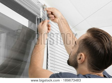 Man installing window blinds at home, close up
