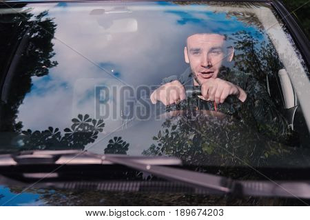 A young man scared screaming at the wheel of the car before the accident. Road traffic accident collision on the road