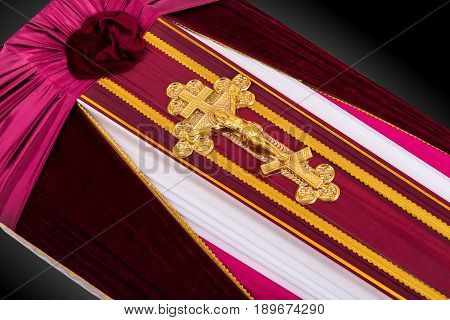 closed coffin covered with purple and white cloth decorated with Church gold cross isolated on gray luxury background. Ritual objects for burial. Surrender body dust of the earth. Close-up details.