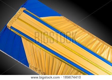 closed yellow and blue coffin covered with elegant cloth isolated on gray background. coffin close-up on royal background. Ritual objects for burial. Surrender body dust of the earth. Christian funeral ritual