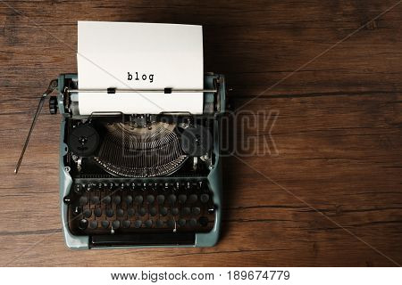 Sheet of paper with word BLOG in typewriter on wooden background