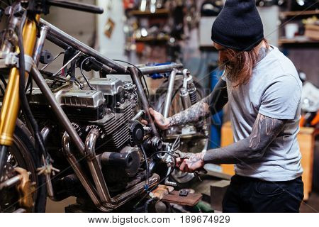 Portrait of focused tattooed man working in garage customizing  motorcycle and repairing broken parts