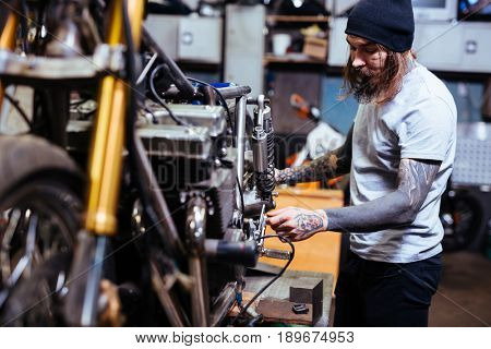 Side view portrait of bearded tattooed mechanic  working in garage customizing  motorcycle and repairing broken parts