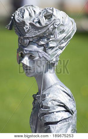 Saint Petersburg, Russia - June 4, 2017: VII international festival of street theatres `Elagin Park`. Living statue lady hiding behind the mask
