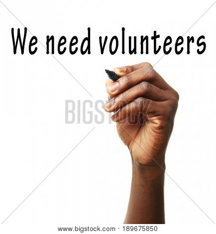 Man writing text WE NEED VOLUNTEERS on white background. Concept of support and help