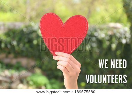 Woman holding red heart and text WE NEED VOLUNTEERS on blurred background. Concept of support and help