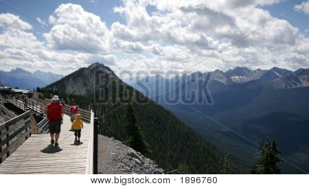 Family Walks Along A Trail On Sulfer Mountain In Banff