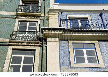 A couple of appartment buildings with fences at the windows in Lisboa.