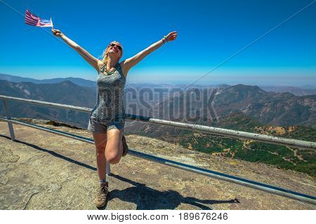 Hiking woman freedom in Sequoia National Park at Moro Rock, a granite dome rock formation. Happy hiker enjoying waving a flag of United States. Summer travel holidays concept. California road trip.