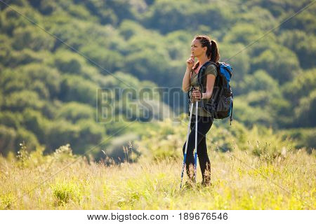 Young woman is hiking in mountain. She is thinking about a way to go.