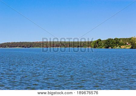 A large lake with a forest on the far shore on a clear summer day