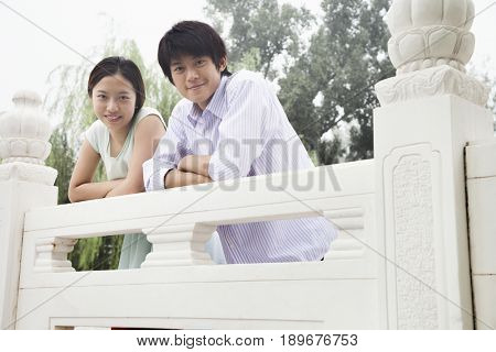 Chinese couple leaning on railing