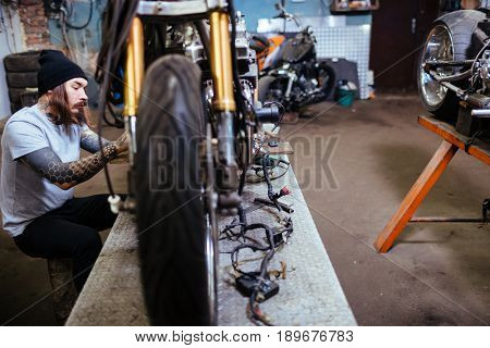 Side view portrait of tattooed man repairing and customizing motorcycles