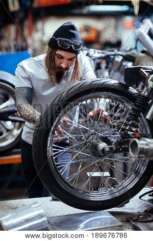 Portrait of modern  tattooed man working in garage customizing  motorcycle and repairing broken wheel mechanism