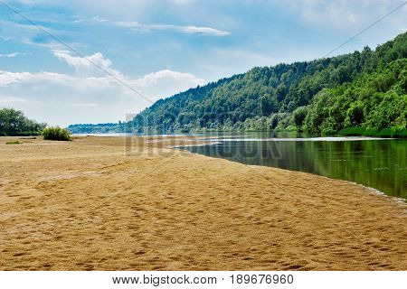 River with a sandy beach and willow bushes on the opposite bank