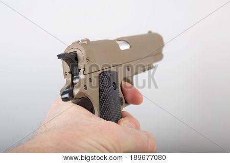 Hand holding modern brown air gun pistol