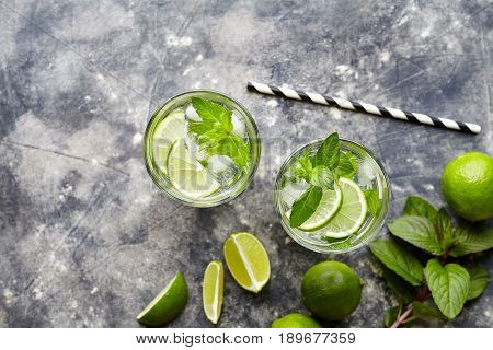 Mojito Cuba highball cocktail non alcohol drink, summer tropical vacation beverage with rum, peppermint mint, lime juice, soda water, sugar and crushed ice on concrete background