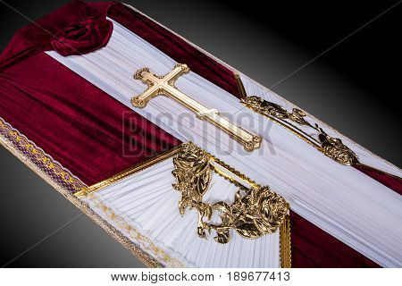 closed coffin covered with bordo and white cloth decorated with Church gold cross isolated on gray luxury background. Ritual objects for burial. Surrender body dust of the earth. Close-up details.