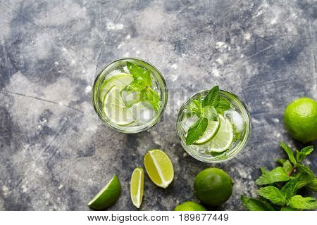 Mojito Cuba cocktail non alcohol drink two highballs, summer tropical vacation beverage with rum, peppermint mint, lime juice, soda water, sugar and crushed ice on concrete background. Top view